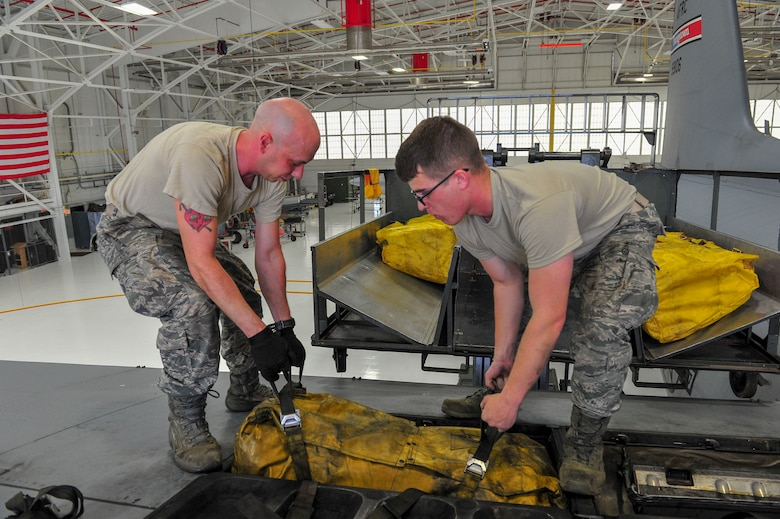 Airman Dustin Bruce and Senior Airman William Hizer, both aircraft maintenance technicians with the 910th Aircraft Maintenance Squadron, remove a 40-person life raft from a compartment on the wing of a C-130H Hercules aircraft here, June 13, 2018.