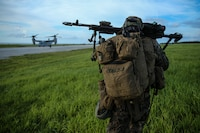 Pfc. Braeden Martin, a machine gunner with Fox Company, Battalion Landing Team, 2nd Battalion, 5th Marines, and a native of Moore, Oklahoma, moves toward a waiting MV-22B Osprey tiltrotor aircraft after completing a simulated helicopter raid as part of the 31st Marine Expeditionary Unit's MEU Exercise at Ie Shima Training Facility, Okinawa, Japan, June 25, 2018. MEUEX is the first in a series of pre-deployment training events that prepare the 31st Marine Expeditionary Unit to deploy at a moment's notice. The 31st MEU, the Marine Corps' only continuously forward-deployed MEU, provides a flexible force ready to perform a wide-range of military operations.