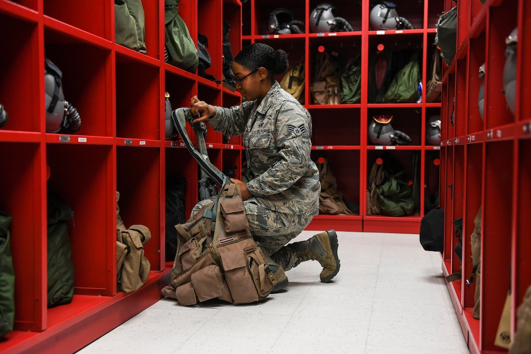 Senior Airman Zilcia Williams, 5th Operations Support Squadron aircrew flight equipment journeyman, inspects life preserver equipment at Minot Air Force Base, N.D., June 19, 2018. (U.S. Air Force photo by Senior Airman Jonathan McElderry)