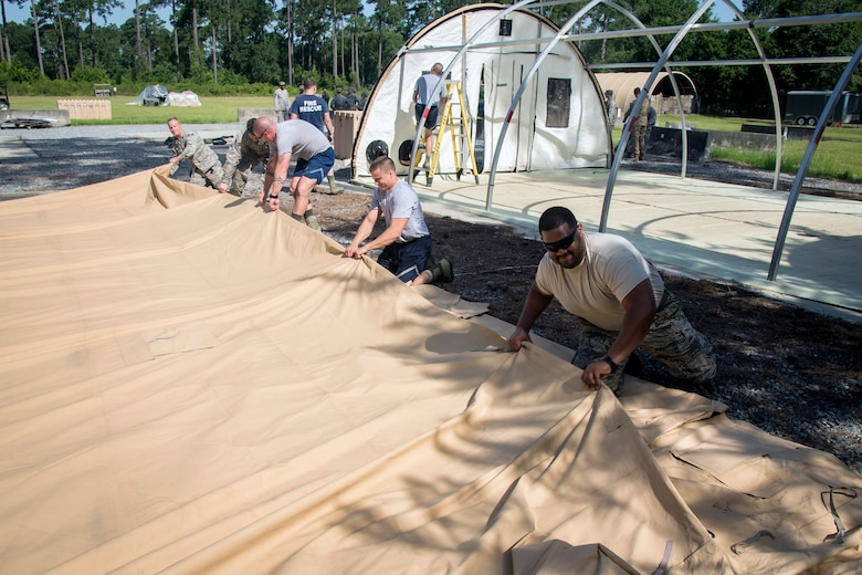Airmen from the 23d Civil Engineer Squadron, fold up a tarp during a chemical, Biological, Radiological, Nuclear and Explosive (CBRNE) Olympics, June 21, 2018, at Moody Air Force Base, Ga.  Moody's first CBRNE Olympics, were held to further Airmen's overall knowledge on all of the aspects of CBRNE through a new method that was meant to establish a sense of competition and camaraderie. (U.S. Air Force photo by Airman 1st Class Eugene Oliver)
