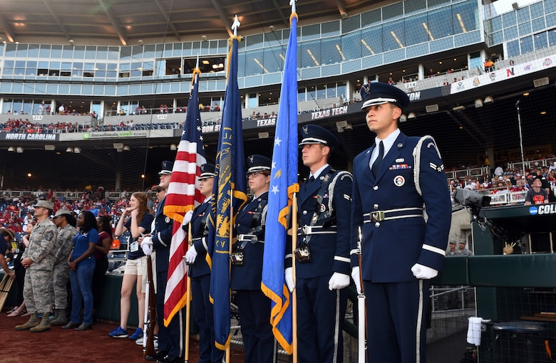 The Offutt honor guard wait by the third-base dugout of TD Ameritrade Park for the National Collegiate Athletic Association Men's College World Series game at TD Ameritrade Park Omaha, Nebraska, June 26, 2018.