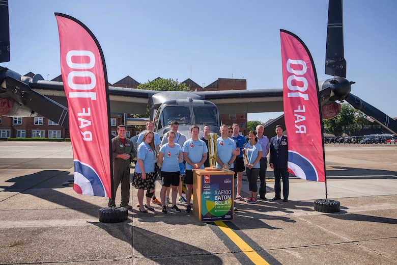 A Royal Air Force baton relay team from the 54th Signals Unit, RAF Digby, pose for a photograph during their visit to RAF Mildenhall, England, for the RAF 100 Baton Relay, June 29, 2018. The team is one of many who ran 54 kilometers at several bases during the relay. (U.S. Air Force photo by Senior Airman Christine Groening)