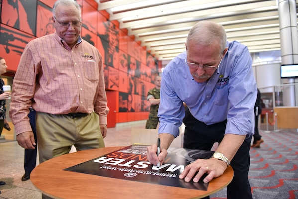 Steve Murphy, right, and Javier Peña autograph a poster at the conclusion of their visit to the Defense Intelligence Agency headquarters, June 21.