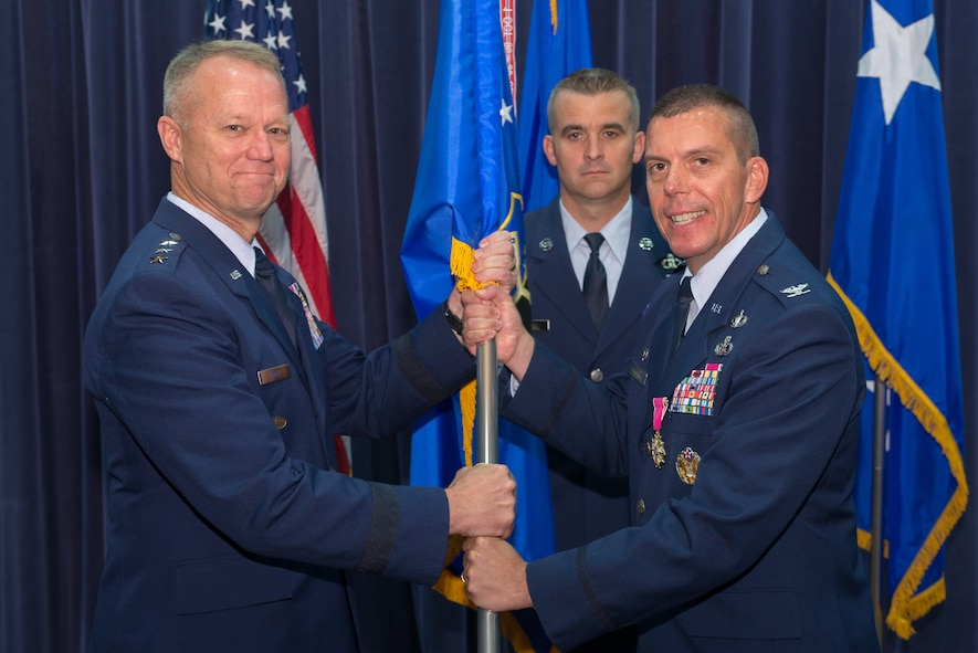 U.S. Air Force Col. Steven Dickerson, outgoing commander, 557th Weather Wing (WW), relinquishes the 557th WW to U.S. Air Force Lt. Gen. Mark Kelly, commander, 12th Air Force, during a change of command ceremony June 26, 2018, at Offutt Air Force Base, Nebraska. The 557th WW has 18 geographically-separated units located around the world. (U.S. Air Force photo by Paul Shirk)