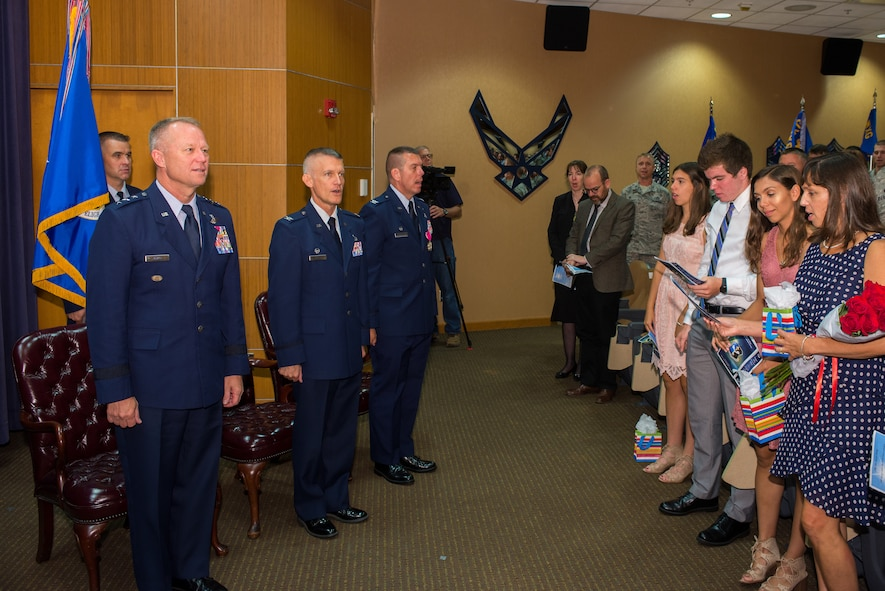 U.S. Air Force Lt. Gen. Mark Kelly, commander, 12th Air Force, U.S. Air Force Col. Brian Pukall, commander, 557th Weather Wing (WW), and U.S. Air Force Col. Steven Dickerson, outgoing commander, 557th WW, sing the Air Force song with audience members at the conclusion of the 557th WW change of command ceremony June 26, 2018, at Offutt Air Force Base, Nebraska. The 557th WW is the Air Force's only weather wing.