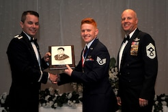 Col. Jeffrey Nelson, left, 628th Air Base Wing commander, and Chief Master Sgt. Todd Cole, right, 628th Air Base Wing command chief, present Staff Sgt. Clayton Cupit, 1st Combat Camera Squadron, a plaque for earning the John L. Levitow Award during the class 18-E Airman Leadership School Graduation at the Charleston Club here June 29, 2018.