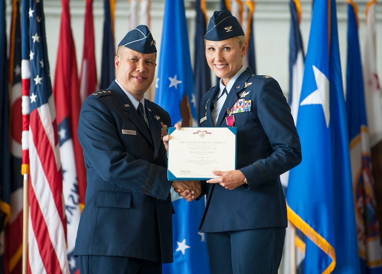 U.S. Air Force Lt. Gen. GI Tuck, 18th Air Force commander, presents a Legion of Merit to Col. April Vogel, the 6th Air Mobility Wing commander before her change of command ceremony at MacDill Air Force Base, Fla., June 29, 2018.
