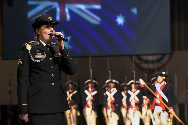 "Army Sgt. Vicki Golding, a vocalist with the District of Columbia Army National Guard's 257th Army Band, sings the Australian national anthem as part of the Centenary of Mateship celebration during the Twilight Tattoo, June 27, 2018, at Joint Base Myer-Henderson Hall, Virginia. Golding, an Australian native who now lives in the U.S., also performed ""The Star-Spangled Banner,"" and ""I Am Australian"" at the event, which commemorated the 100-year anniversary of the partnership between the United States and Australia established during World War I."