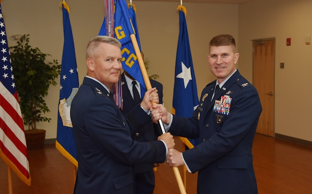 Col. Michael A. Sinks accepts command of the 844th Communications Group from Maj. Gen. James A Jacobson, Air Force District of Washington commander, during a change-of-command ceremony June 28 on Joint Base Andrews, Maryland.