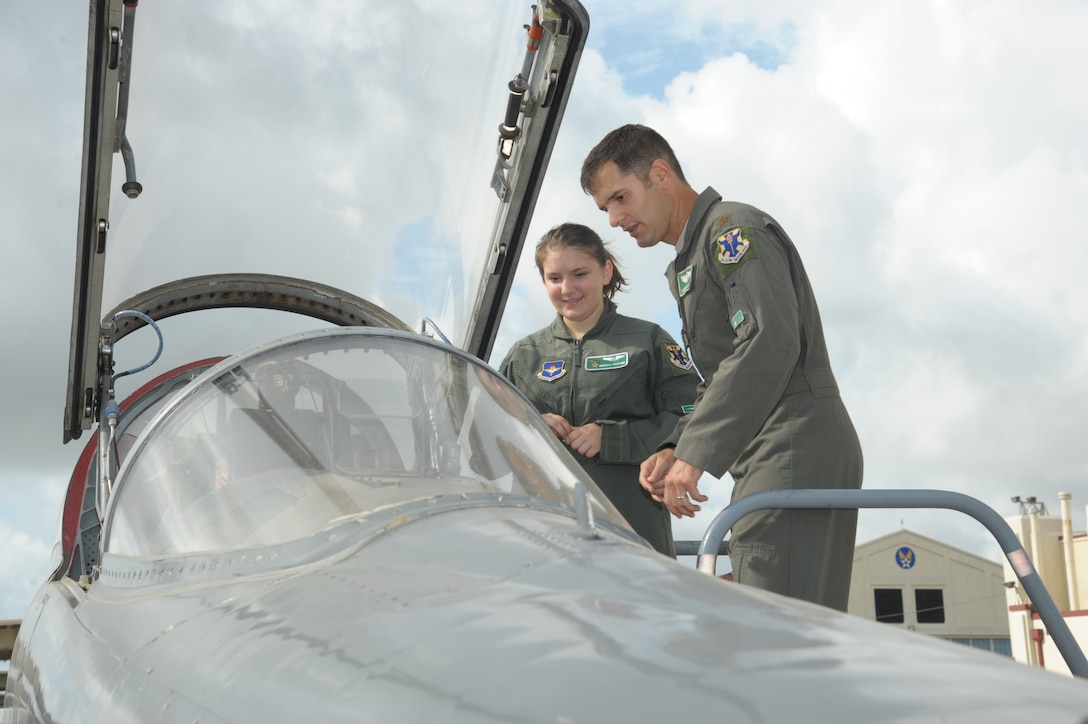"""Maj. Justin Stimets, 560th Flying Training Squadron instructor pilot, speaks with Megan Foster aboard a T-38 Talon during her """"Pilot for a Day"""" orientation June 26, 2018, at Joint Base San Antonio-Randolph, Texas.  The """"Pilot for a Day"""" program invites children of all ages, military or civilian, to be guests of the 12th Flying Training Wing and its flying squadrons for an entire day. Doing so, the 12th FTW strives to give each child a special day and a break from the challenges they may face.  (U.S. Air Force photo by Joel Martinez/Released)"""