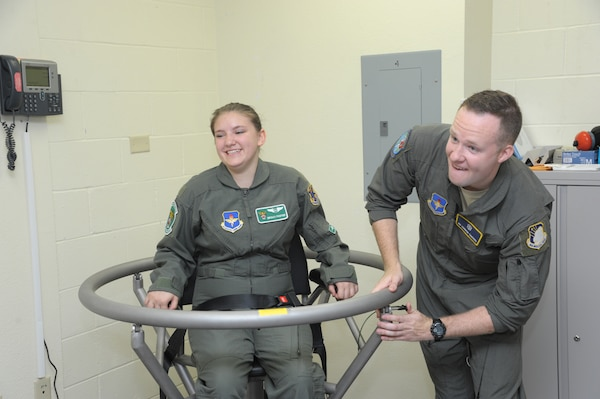 "Airman 1st Class Conner Sanders, 59th Medical Wing aerospace physiology technician, prepares to spin Megan Foster on the Barany Chair during her ""Pilot for a Day"" orientation June 26, 2018, at Joint Base San Antonio-Randolph, Texas.  The ""Pilot for a Day"" program invites children of all ages, military or civilian, to be guests of the 12th Flying Training Wing and its flying squadrons for an entire day. In so doing, the 12th FTW strives to give each child a special day and a break from the challenges they may face.  (U.S. Air Force photo by Joel Martinez/Released)"