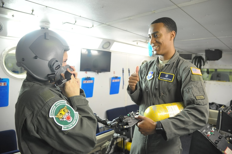 """Airman 1st Class Ckyree Campbell, 59th Medical Wing aerospace physiology technician, speaks about the altitude chamber to Megan Foster, during her """"Pilot for a Day"""" orientation June 26, 2018, at Joint Base San Antonio-Randolph, Texas.  The """"Pilot for a Day"""" program invites children of all ages, military or civilian, to be guests of the 12th Flying Training Wing and its flying squadrons for an entire day. In so doing, the 12th FTW strives to give each child a special day and a break from the challenges they may face.  (U.S. Air Force photo by Joel Martinez/Released)"""