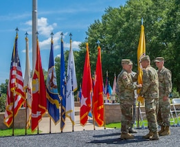 Maj. Gen. Richard Gallant (right), Lt. Gen. Jeffrey Buchanan (center front), Maj. Gen. William Hall (right) and CMSgt James Brown (center back) pass along the Joint Task Force Civil Support (JTF-CS) flag during a Change of Command ceremony on 29 June. The tradition symbolizes the passing of authority from the previous JTF-CS commander (Gallant) to the new commander (Hall), who is now the tenth commander of JTF-CS. JTF-CS provides command and control for designated Department of Defense specialized response forces to assist local, state, federal and tribal partners in saving lives, preventing further injury and providing critical support to enable community recovery. (Official DoD photo by Mass Communication Specialist 3rd Class Michael Redd/released)
