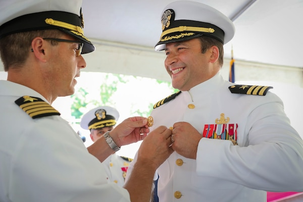 Cmdr. Matthew Myers, EXU-1's inaugural commanding officer, receives his Command at Sea Insignia denoting his new status as a commanding officer.