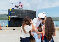 170629-N-PK553-220 SANTA RITA, Guam (June 29, 2018) Chief Electonics Technician Navigation Michael Levy receives a kiss from wife Crystal during a homecoming ceremony on the pier for Los-Angeles class fast attack submarine USS Oklahoma City (SSN 723), June 29. Oklahoma City is one of four forward-deployed submarines assigned to Commander, Submarine Squadron 15.  (U.S. Navy photo by Culinary Specialist Seaman Jonathan Perez)