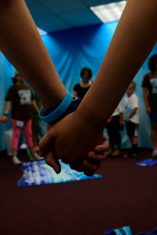 Children hold hands during a closing prayer June 29, 2018 at Fairchild Air Force Base, Washington. Children participated in four daily activity stations during the five-day Vacation Bible School, learning about the teachings of the bible. These lessons also gave the military children important tools to build upon their spiritual resilience in the face of numerous challenges and stressors they encounter on a near daily basis. (U.S. Air Force photo/Staff Sgt. Nick Daniello)
