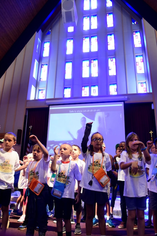 Children sing during Vacation Bible School June 29, 2018 at Fairchild Air Force Base, Washington. All of the activities that children participated in immersed them in faith development. These lessons are not limited to teaching bible verses and songs, they also give military children important tools to build upon their spiritual resilience in the face of the numerous challenges and stressors they encounter on an almost daily basis. (U.S. Air Force photo/Staff Sgt. Nick Daniello)