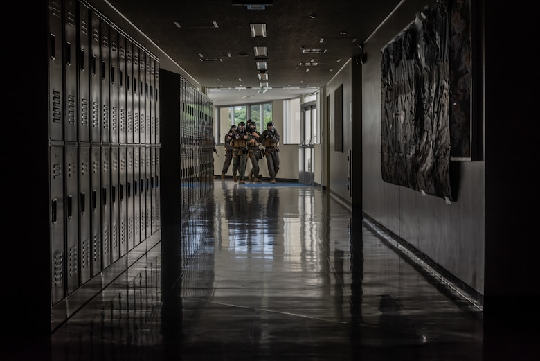 U.S. Marine Corps Marines from the Provost Marshal's Office special reaction team clears a hallway during an active shooter training exercise June 25, 2018, at Ryukyu Middle School, Kadena Air Base, Japan. The exercise enabled 18th Security Forces Squadron defenders to work with a U.S. Marine Corps special reaction team and the Kadena Fire Department to hone their skills. (U.S. Air Force photo by Staff Sgt. Micaiah Anthony)