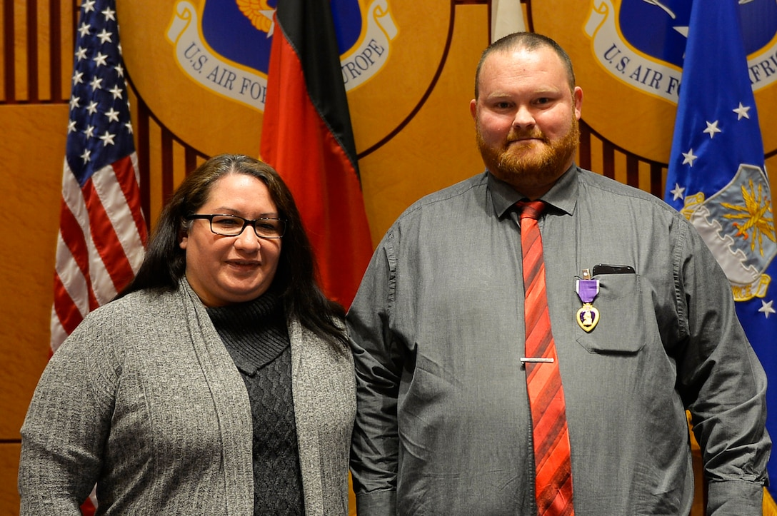 Judson Rackley, U.S. Air Forces in Europe-Air Forces Africa video operations center communications engineer, right, poses for a picture with his wife, Audrea, after receiving the Purple Heart on Ramstein Air Base, Germany, Feb. 27, 2018. Rackley previously served in the U.S. Army, where he took part in missions in Afghanistan. (U.S. Air Force photo by Senior Airman Joshua Magbanua)