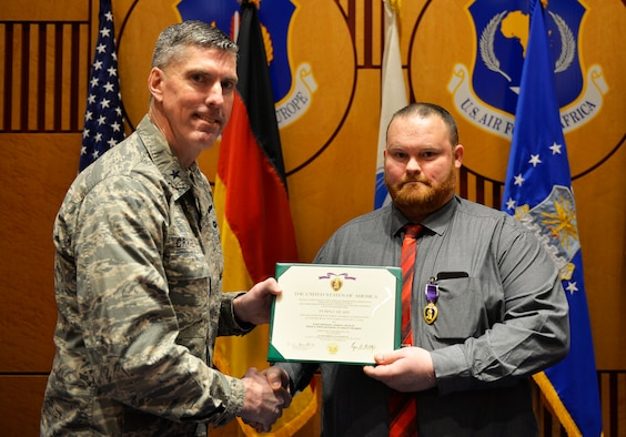 Judson Rackley, U.S. Air Forces in Europe-Air Forces Africa video operations center communications engineer, right, receives the Purple Heart from U.S. Air Force Brig. Gen. Christopher Craige, USAFE-AFAFRICA chief of staff on Ramstein Air Base, Germany, Feb. 27, 2018. The Purple Heart is awarded to veterans and military members for wounds received or death after being wounded in action against enemy forces. (U.S. Air Force photo by Senior Airman Joshua Magbanua)