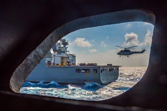 A ship's port hole shows a helicopter flying near another ship in the ocean.