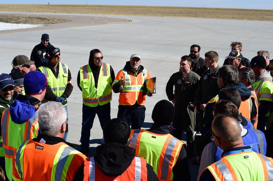 Joe Rashid, Lockheed Martin certified test conductor, briefs members from Lockheed Martin on the loading operations of the Interior Exploration using Seismic Investigations, Geodesy and Heat Transport lander onto a Boeing C-17 Globemaster III Feb. 28, 2018, on Buckley Air Force Base, Colorado. The lander itself weighs 14,500 pounds and has an estimated cost of 500 million dollars. (U.S. Air Force photo by Senior Airman Luke W. Nowakowski)