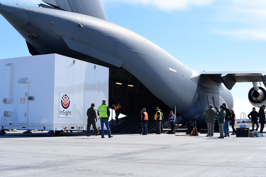 Members from Lockheed Martin carefully observe the Interior Exploration using Seismic Investigations, Geodesy and Heat Transport lander being loaded onto a Boeing C-17 Globemaster III Feb. 28, 2018, on Buckley Air Force Base, Colorado. The measurements taken by the lander while on the surface of Mars will give scientists more insight into the origins of our planets and solar system. (U.S. Air Force photo by Senior Airman Luke W. Nowakowski)