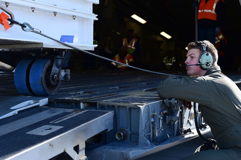 Senior Airman Griffin Brewer, 21st Airlift Squadron loadmaster, makes sure the Interior Exploration using Seismic Investigations, Geodesy and Heat Transport lander is properly aligned while being loaded onto a C-17 Globemaster III Feb. 28, 2018, on Buckley Air Force Base, Colorado. Thousands of hours, hundreds of people, and millions of dollars went into producing the InSight lander so it is imperative that all operations go according to plan. (U.S. Air Force photo by Senior Airman Luke W. Nowakowski)