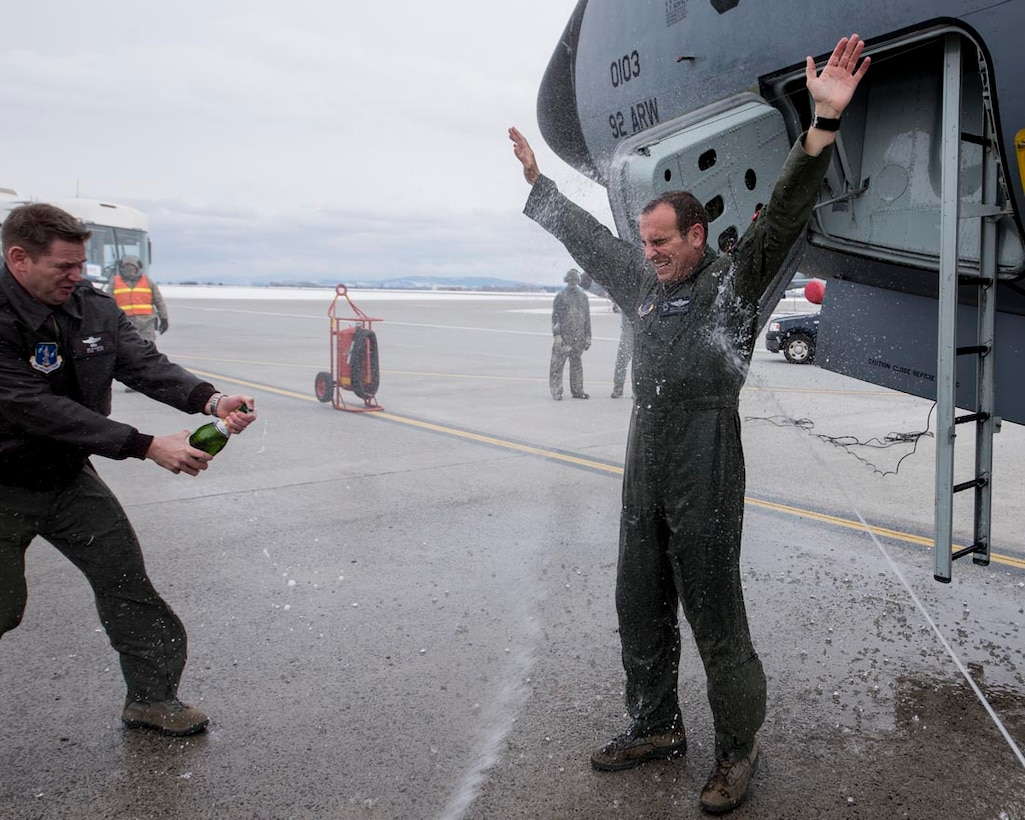 Col. Matthew Yakely, commander of the 141st Operations Group, is sprayed with water and champagne after completing his final flight on a KC-135 Stratotanker February 23, 2018 at Fairchild Air Force Base, Wash. The final flight, or fini-flight, is a tradition among pilots and air crew to celebrate one's last flight with their unit or on a certain airframe.