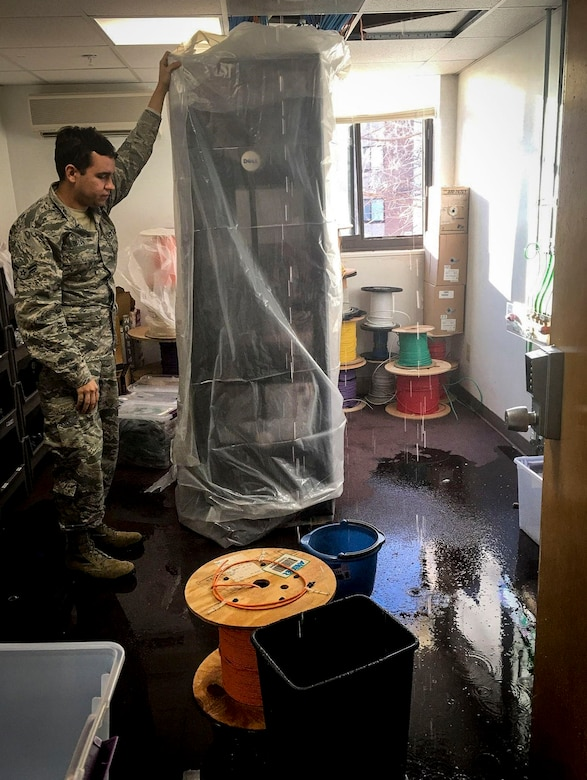 Airman 1st Class Jeremy Buzan, 707th Communications Squadron Cyber Systems Operations Technician, protected network servers from water-damage from a leak in Building 9801B on Jan. 2, 2018 at Fort Meade, Md. Several 707th CS Airmen pulled a 24-hour shift to rebuild damaged equipment and prevent further water damage.  The joint team effort from the 707th CS and 70th ISRW Civil Engineer fully restored non-secure network services in less than 27 hours and fully restored secure network services in less than 10 hours. (Courtesy Photo)