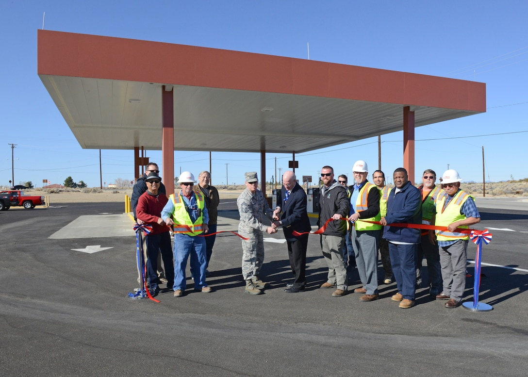 Center: Chief Master Sgt. Daniel Thompson, 412th Mission Support Group superintendent, and James Judkins, 412th Civil Engineer Group director, cut the ceremonial ribbon to celebrate the completion of major repairs and upgrades to the main base military gas station at Edwards Feb. 26. The completion of the project is the last of nine projects funded by the DLA for repairs and upgrades to facilities on Edwards. (U.S. Air Force photo by Kenji Thuloweit)