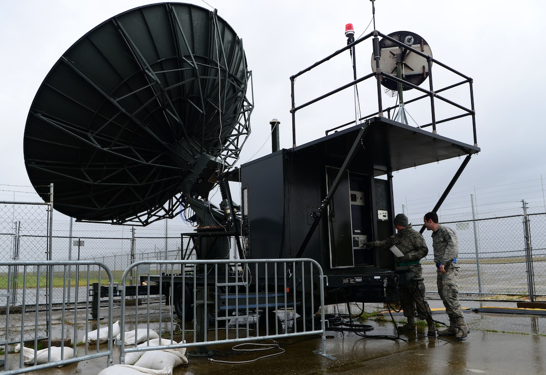 Senior Airman Christopher Good and Senior Airman Lauryn Gormaly, 9th Aircraft Communications Maintenance Unit ground communication segment technicians, stow an antenna due to inclement weather