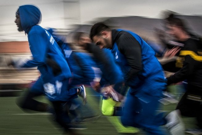 Airmen in blue athletic gear warm up before a sprint track event.