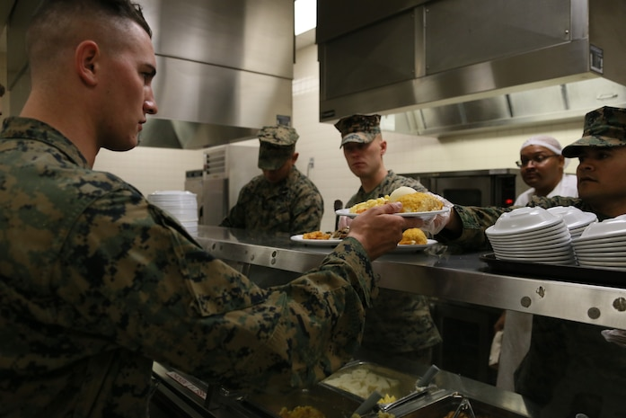 SSgt Anthony W. Oliva, SSgt Wade W. Mayhew, and GySgt Edward Dominguez (From left to right), Motor Transport Instructors, assist serving meals for students on the Marine Corps 242nd Birthday at Fort Leonard Wood, MO Nov. 10th, 2017. By leading by example, the Instructors recognize the students as future leaders of the Marine Corps. (U.S. Marine Corps photo by Sgt. Teng Yang)