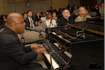 Key Arts Productions' Joe Patterson (left foreground) plays piano and sings to accompany a video presentation of African-Americans in times of war at Defense Logistics Agency Troop Support in Philadelphia on Feb. 28.