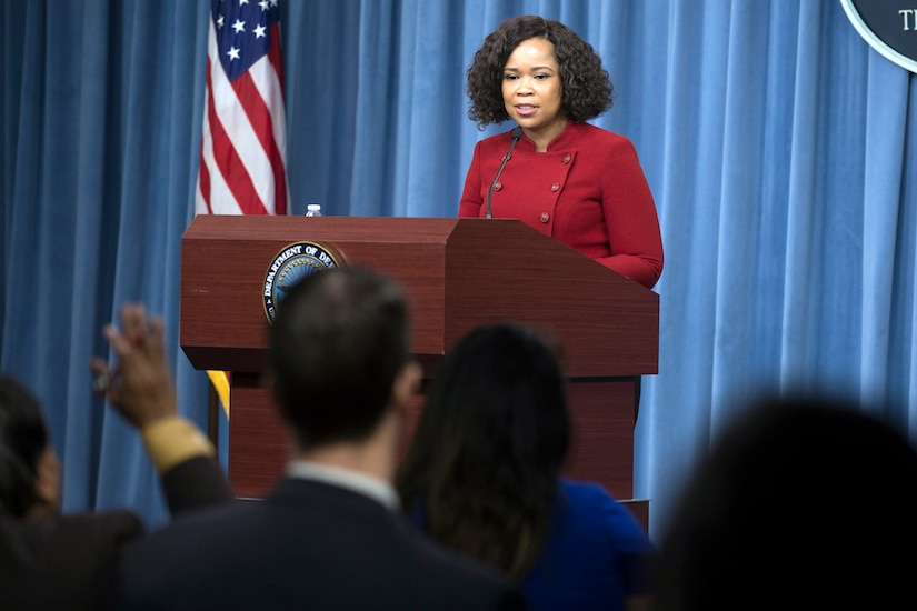 The chief Pentagon spokesperson briefs reporters from behind a podium.