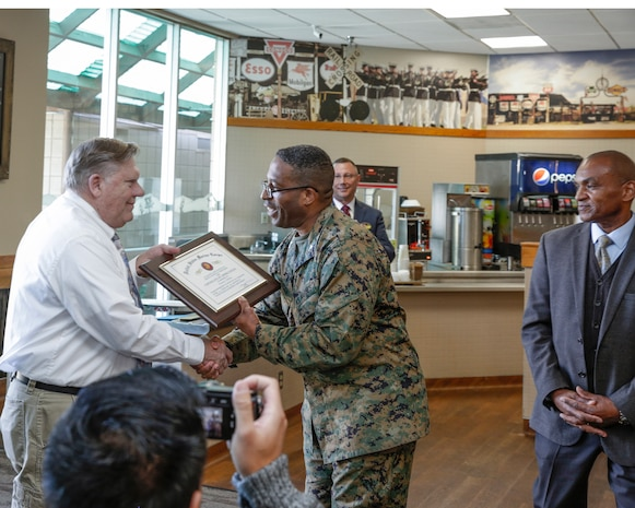 Francis Villeme, personal and professional development program manager, receives a certificate of appreciation from Col. Sekou Karega, base commander, during his retirement luncheon in the Route 66 Café aboard Marine Corps Logistics Base Barstow, Calif., Feb. 22.