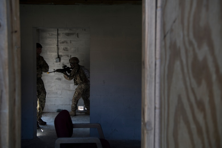 An Airman from the 824th Base Defense Squadron guards the entrance to a building while British Royal Air Force Sgt. Glenn Risebrow, left, 15th Squadron senior noncommissioned officer in charge of training, observes during close-quarters battle training, Feb. 28, 2018, at Moody Air Force Base, Ga. The 820th Base Defense Group welcomed a member of the British Royal Air Force to embed into multiple training situations to help strengthen combined operations between U.S. and British forces. (U.S. Air Force photo by Senior Airman Daniel Snider)