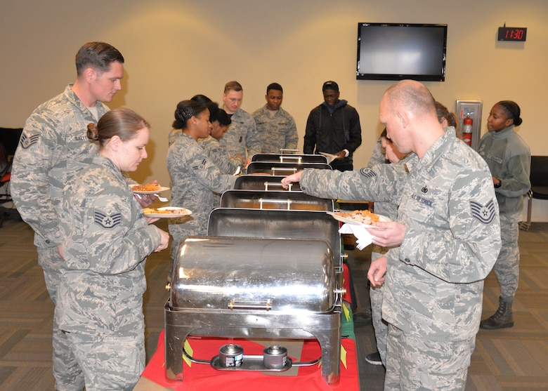 Airmen line up to sample food during a cultural exposé at Ellsworth Air Force Base, S.D., Feb. 23, 2018.  The event allowed attendees to taste traditional West African cuisine and experience African culture. (U.S. Air Force photo by Senior Airman Michella T. Stowers)
