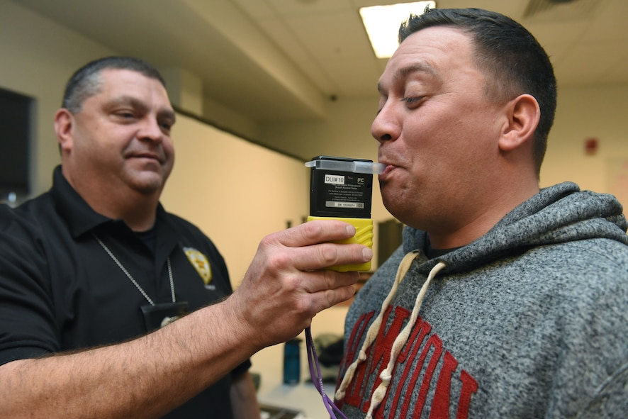 Officer Javen Owens, Aurora Police Department Traffic Unit, uses a breathalyzer to test the blood alcohol content of Master Sgt. Rodney Franken, National Reconnaissance Office/Detachment 3 Security Operations superintendent, during a Standardized Field Sobriety Training, Feb. 12, 2018, on Buckley Air Force Base. Breathalyzers were used before administering the sobriety tests to show just how impaired each individual would be in a driving situation. (U.S Air Force photo by Senior Airman AJ Duprey)