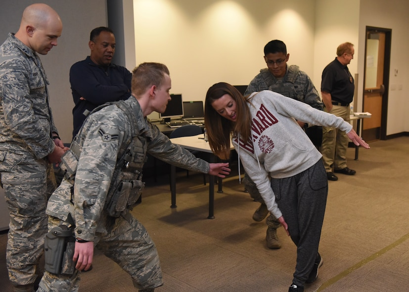 Tech. Sgt. Cassidy Wong, National Reconnaissance Office/Detachment 3 NCOIC Executive Support, falters in the midst of a field sobriety test as two security forces Airmen swoop in to catch her during Standardized Field Sobriety Training, Feb. 12, 2018, on Buckley Air Force Base. The 460th Security Forces Squadron participated in 3-day training presented by the Aurora Police Department Traffic Unit where they learned to administer sobriety tests as well as what it's like to be tested in an inebriated state.(U.S Air Force photo by Senior Airman AJ Duprey)