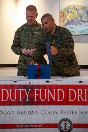 Brig. Gen. Paul Rock Jr., left, and Master Sgt. Aaron Matura prepare the donation box during the Navy-Marine Corps Relief Society Active Duty Fund Drive kick off Feb. 27 aboard Camp Foster, Okinawa, Japan. The Active Duty Fund Drive funds programs offered through the NMCRS like the budget for baby classes and providing interest free loans.  Rock is the commanding general of Marine Corps Installations Pacific-Marine Corps Base Camp Butler, Japan. Matura is the coordinator for the Active Duty Fund Drive. (U.S. Marine Corps photo by Pfc. Nicole Rogge)
