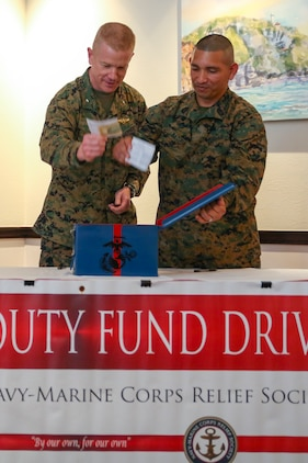 Brig. Gen. Paul Rock Jr., left, and Master Sgt. Aaron Matura place their donations into donation box to kick off the Navy-Marine Corps Relief Society Active Duty Fund Drive Feb. 27 aboard Camp Foster, Okinawa, Japan. The Active Duty Fund Drive funds programs offered through the NMCRS like the budget for baby classes and providing interest free loans. Rock is the commanding general of Marine Corps Installations Pacific-Marine Corps Base Camp Butler, Japan. Matura is the coordinator for the Active Duty Fund Drive kick off. (U.S. Marine Corps photo by Pfc. Nicole Rogge)