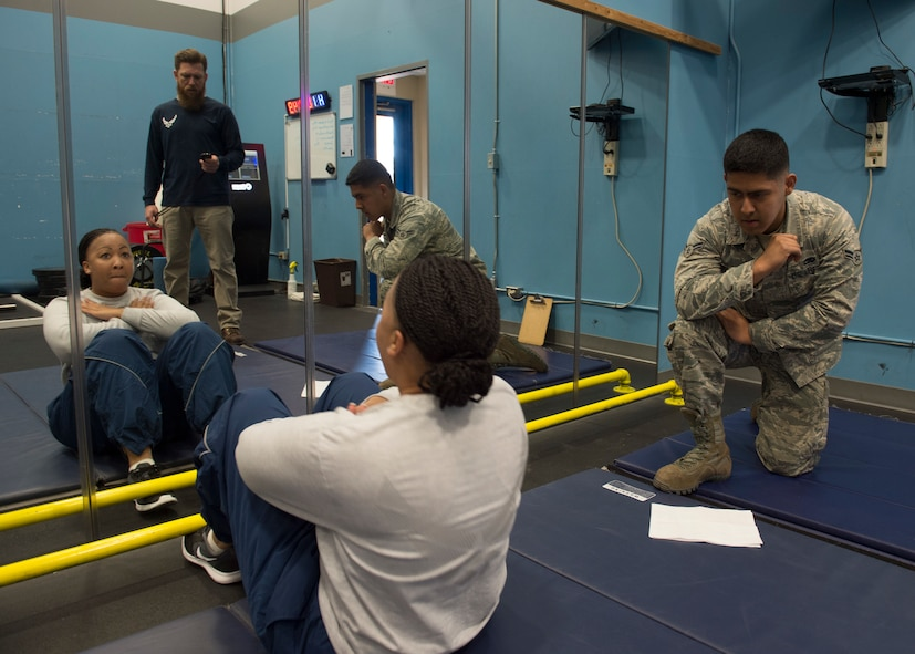 U.S. Air Force Airman 1st Class Melchor Philip, a traffic management Airman assigned to the 97th Logistics Readiness Squadron, counts repetitions for the sit-up portion of the physical training test, March 1, 2018, at Altus Air Force Base, Okla.