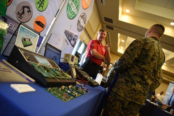 Jana Asplund, Nida Corporation Technical Specialist, talks to Keesler Marine Detachment Marines about products during the 2018 Keesler Technology Expo at the Bay Breeze Event Center Feb. 27, 2018, on Keesler Air Force Base, Mississippi. The expo was hosted by the 81st Communications Squadron and was free to all Defense Department, government and contractor personnel with base access. The event was held to introduce military members to the latest in technological advancements to bolster the Air Force's capabilities in national defense. (U.S. Air Force photo by Airman 1st Class Suzanna Plotnikov)