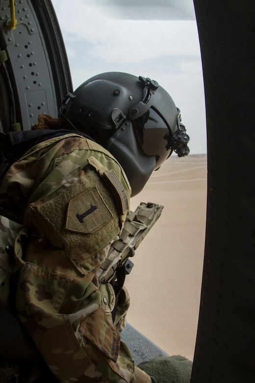"""Staff Sergeant Jackie Edwards, crew chief, Alpha Company, """"Task Force Voodoo"""", 1st Assault Helicopter Battalion, 244th Aviation Regiment, Louisiana National Guard during a flight over Camp Buehring, Kuwait, Feb. 27, 2018. Edwards, a Ponchatoula, Louisiana, native, is the first African-American female crew chief in the LANG."""