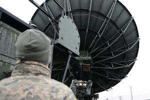 An airman looks up at a large satellite antenna.