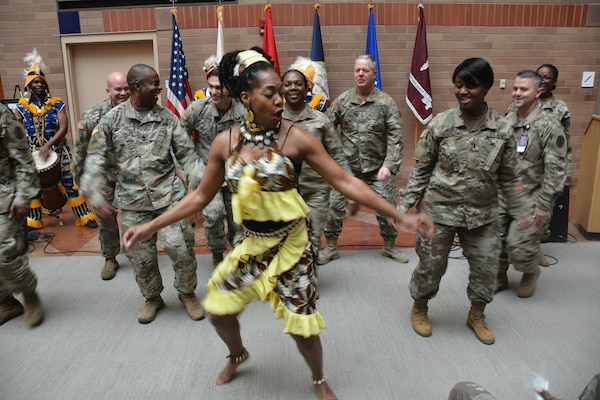The Bramaya dance and drum troupe from Austin, Texas, entertains the audience with traditional West African music and dance at the Black History Month observance at Brooke Army Medical Center at Joint Base San Antonio-Fort Sam Houston Feb. 22. The dance troupe encouraged members of the audience to join them in the festivities.