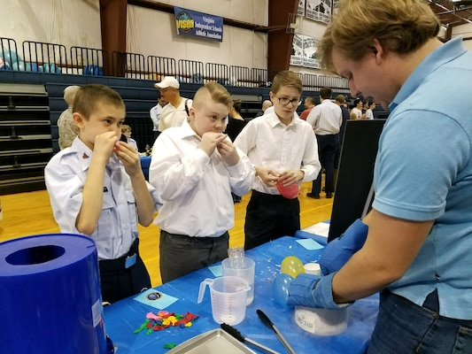 IMAGE: FREDERICKSBURG, Va. - Navy engineer Josh Taylor conducts a liquid nitrogen demonstration with students at the science, technology, engineering and mathematics (STEM) Summit hosted by the Fredericksburg Academy, Feb. 24. Taylor - a Naval Surface Warfare Center Dahlgren Division (NSWCDD) STEM mentor - and the students discussed the Ideal Gas Law, and how it relates different attributes of a fluid. In the picture, they are exposing the inflated balloons to liquid nitrogen and observing that the volume of air inside the balloons decreased as the temperature decreased. Taylor and the students then discussed and demonstrated how changes in temperature could be used to produce kinetic energy, and how temperature changes could affect the behavior of materials. For example, they made flowers shatter like glass, tennis balls that would not bounce, and rubber bands that cracked. 