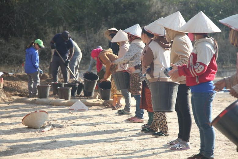 Lao workers assist U.S. service members by lining up with buckets to move dirt to screening stations, where they examined it to locate any belongings and remains of Airmen missing in action since the Vietnam War.